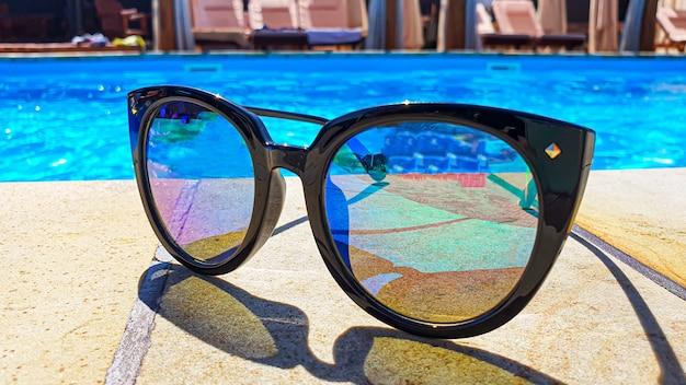 Veiligheidsbril op de borstwering bij het zwembad
