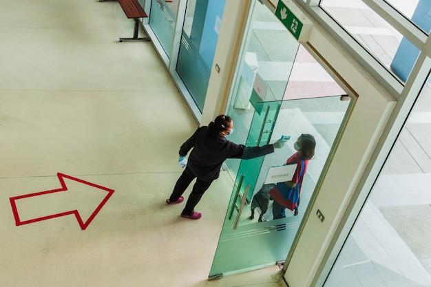Veiligheidscontrole temperatuur door het gebouw van de toegangsdeur van de bezoekers van de thermometer