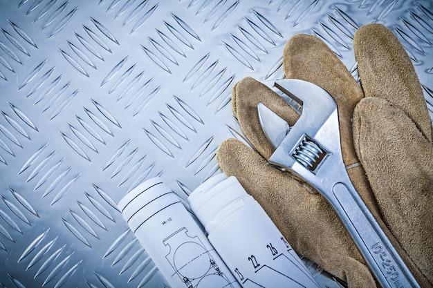 Veiligheidshandschoenen gerold constructietekeningen verstelbare sleutel op gegroefde metalen achtergrond