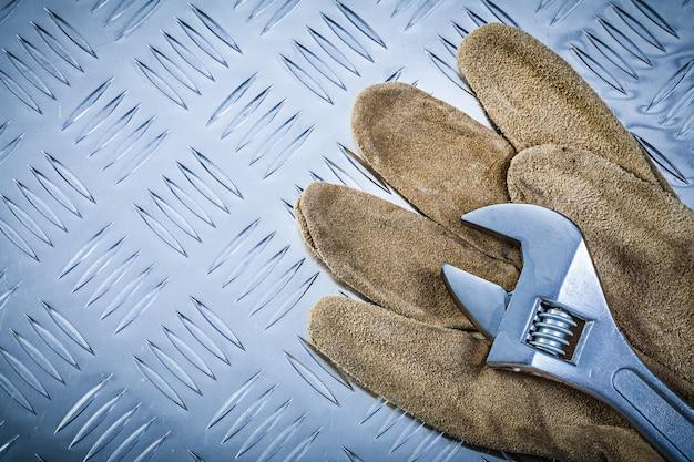 Veiligheidshandschoenen verstelbare sleutel op gegroefde metalen plaat