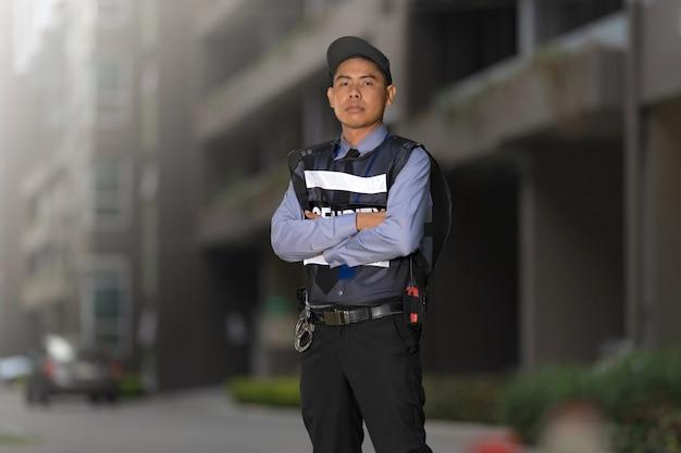 Veiligheidsmens die zich in openlucht dichtbij groot gebouw bevinden