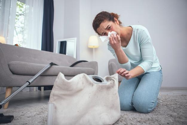 Veiligheidsschending. adolescente vrouw die vatbaar is voor stofallergieën die lijdt aan de gevolgen van het niet dragen van persoonlijke beschermingsmiddelen tijdens het schoonmaken van vuil tapijt