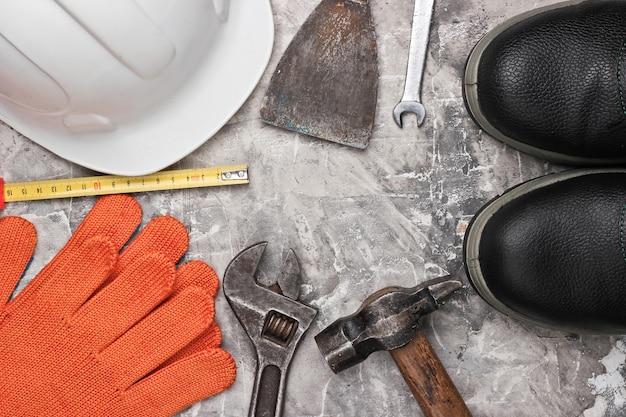 Veiligheidsuitrusting en werkinstrument op grijze betonnen achtergrond. bovenaanzicht. kopieer ruimte