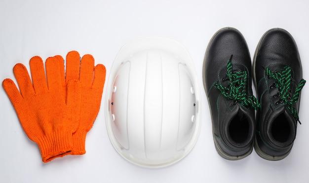 Veiligheidsuitrusting op een witte achtergrond. bouwhelm, werk lederen laarzen, handschoenen op een witte achtergrond. bovenaanzicht