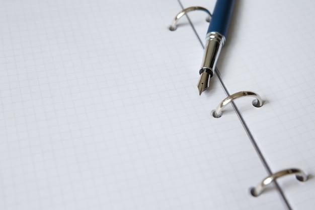 Vel notitieboekje of dagboek in kooi open schoolnotitieboekje met ringen metalen vulpen
