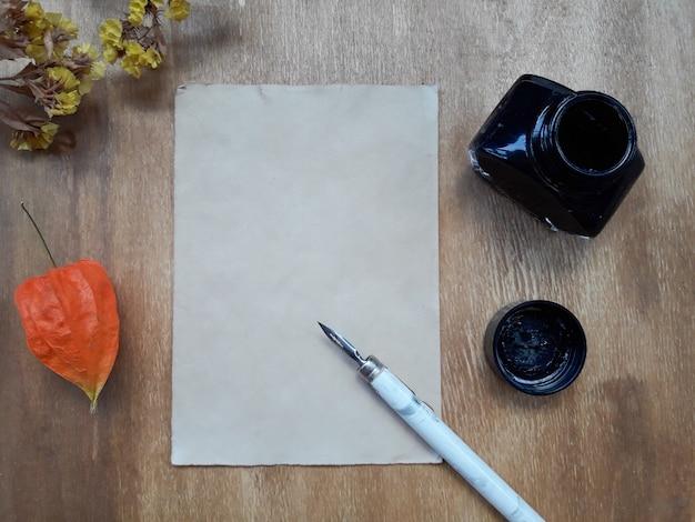 Vel papier, een inktpot en droge bloemen