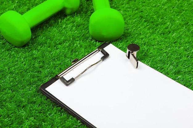 Vel papier en sportartikelen op gras close-up