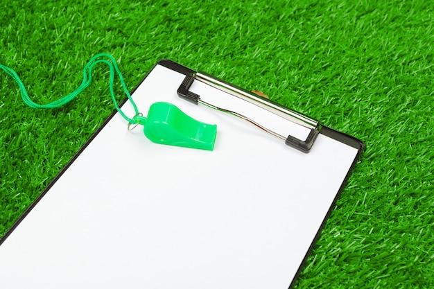 Vel papier en sportuitrusting op gras close-up