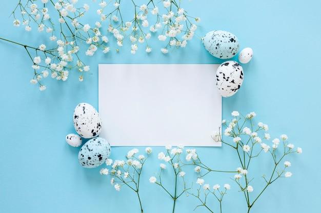 Vel papier op tafel naast beschilderde eieren en bloemen