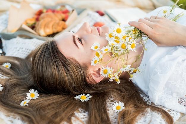Veld in madeliefjes, een boeket bloemen. zomerpicknick aan zee. mand voor een picknick met broodjes, appels en sap. meisje op een picknick ligt en leest een boek