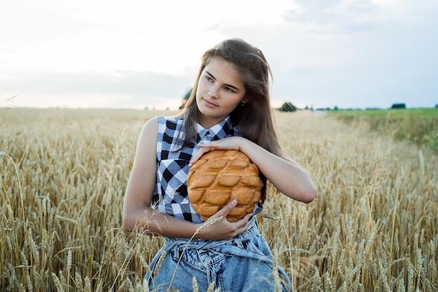 Veld met korenaren, oogst van brood. tienermeisje dat rond brood houdt. brood selectieve aandacht. handen met groot brood. bakkerijproducten op een tarweveld.