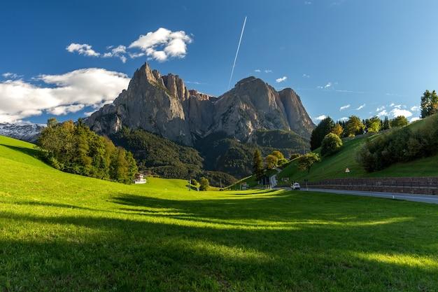 Veld omgeven door rotsen bedekt met groen onder een blauwe lucht en zonlicht in italië