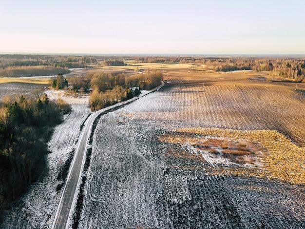 Velden gedeeltelijk bedekt met sneeuw op zonnige lentedag, luchtfoto