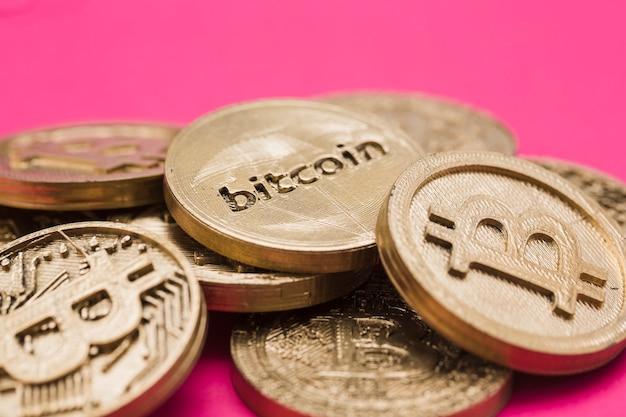Vele bitcoins tegen roze achtergrond