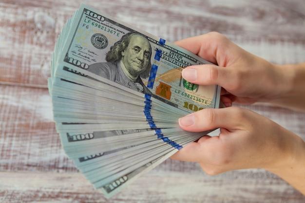 Vele dollars die op de hand van de vrouw met geld vallen