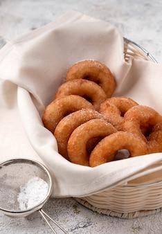 Vele donuts in een rieten mand, huisbaksel, rustieke stijl