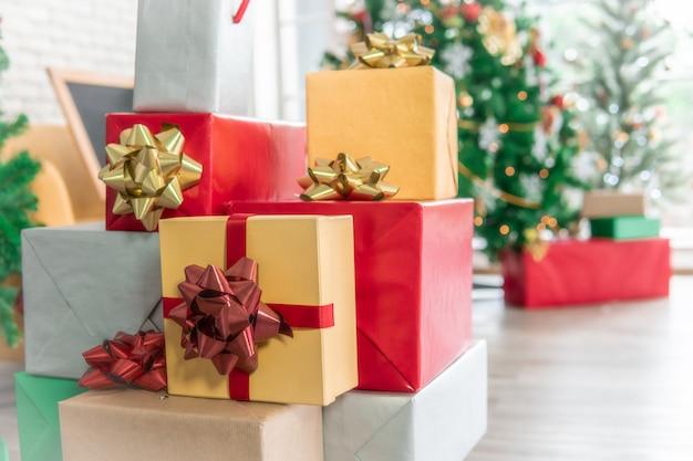 Vele dozen van de kerstmisgift met grote rode en gele bogen voor bokeh van fonkelende de partijlichten van de kerstboom.