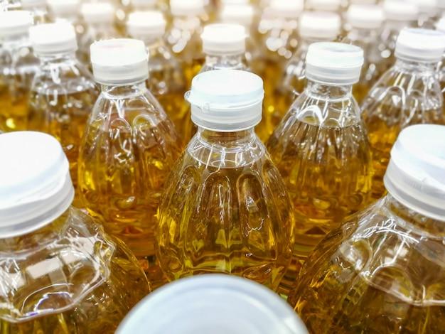 Vele flessen in rijstapel plantaardige olie op de planken in supermarktmateriaal