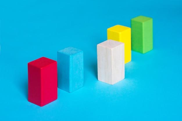 Vele gekleurde blokken op een rij en één houten blok op blauwe achtergrond