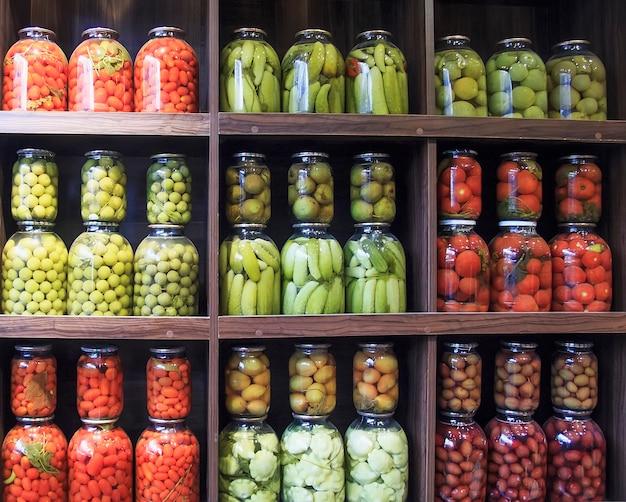 Vele glasflessen met bewaard voedsel in houten kabinet.