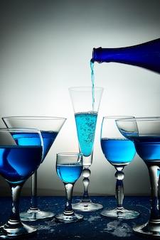 Vele glazen met blauwe champagne of cocktail.