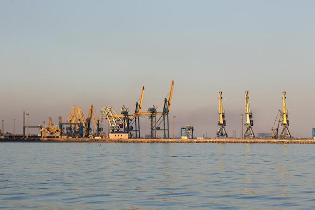 Vele grote kranen silhouetteren in de haven bij gouden licht van zonsondergang. mariupol, oekraïne