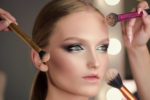 Vele handen maken tot jonge vrouw. natuurlijke huid, natuurlijke make-up.