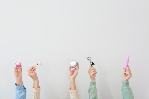 Vele handen met cosmetica en benodigdheden op lichte ondergrond