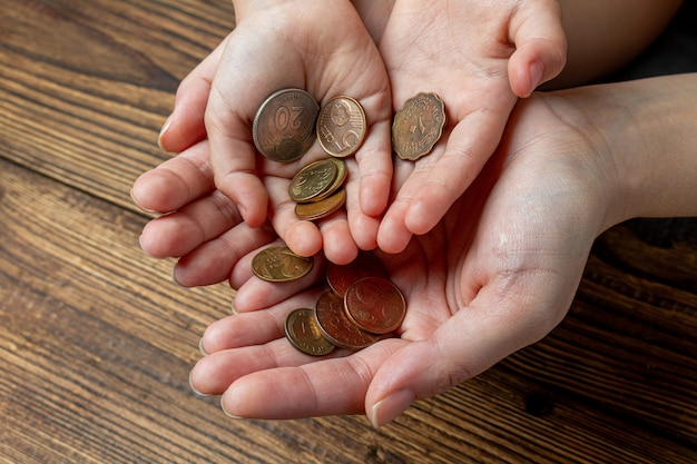 Vele handen met munten in de handpalmen