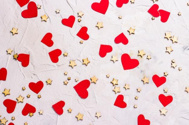 Vele kleine sterren en rode harten op een lichte steenachtergrond.
