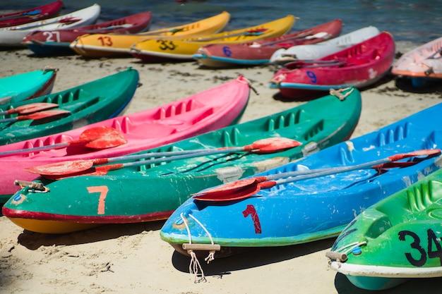 Vele kleurrijke oude kajaks kayaks op het strand