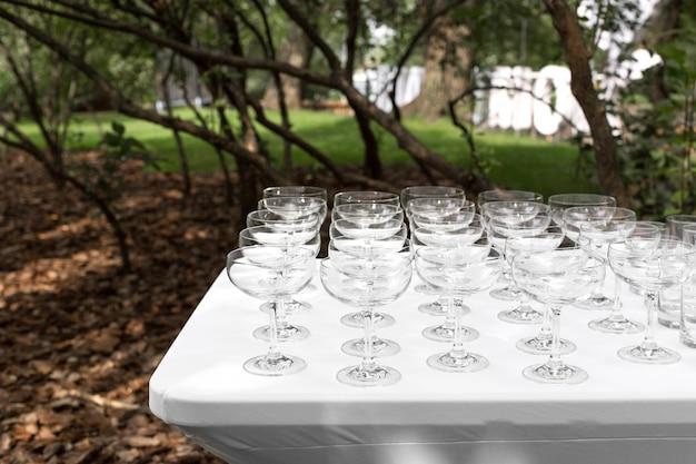 Vele lege schone glazen voor gasten bij de lijst van het buffet feestelijke huwelijk