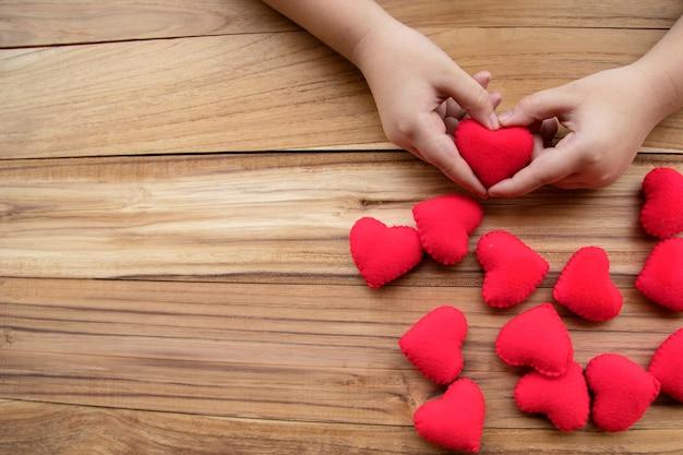 Vele rode harten en jongenshanden houden rood hart op houten achtergrond