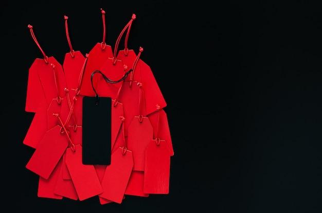 Vele rode prijskaartjes en één zwart prijskaartje bovenop met donkere achtergrond voor black friday-het winkelen verkoopconcept.