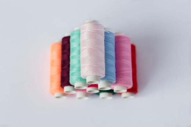 Vele spoelen van heldere naaiende draad met een zachte grijze geïsoleerde achtergrond