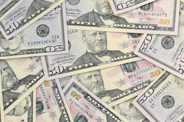 Vele vs vijftig dollarrekeningen op vlakke oppervlakte als achtergrond sluiten omhoog. plat lag bovenaanzicht. abstract bedrijfsconcept