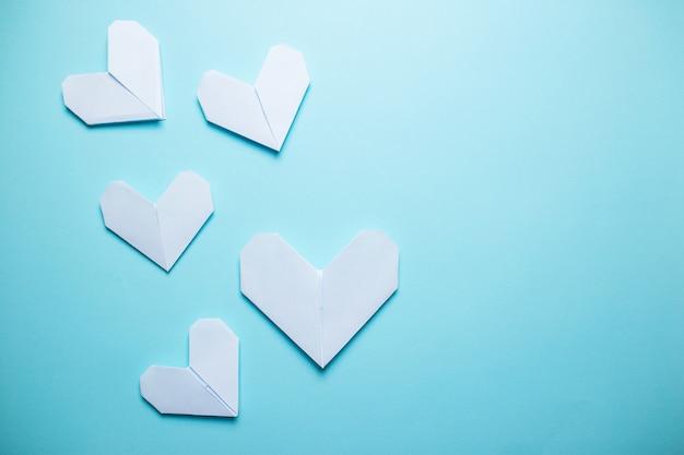 Vele witte origamiharten op blauwe achtergrond. de dagkaart van heilige valentine op blauwe achtergrond.