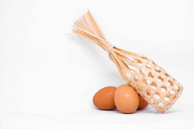 Velen ei (kip) met houten mand die op witte achtergrond wordt geïsoleerd