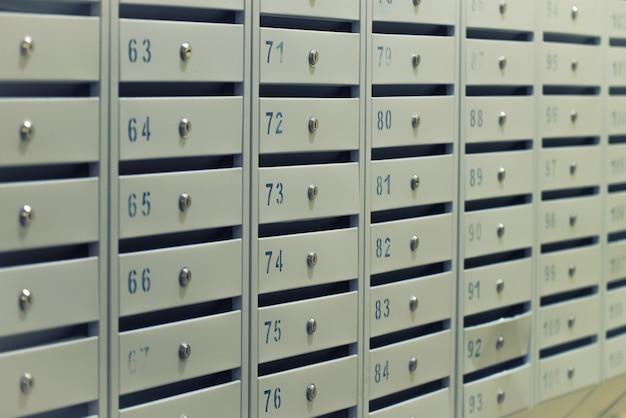Velen posten metalen brievenbussen met kamernummer bij woongebouw