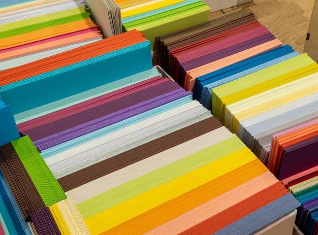 Vellen gekleurd karton voor creatieve ontwerpen van ontwerpers. stapels veelkleurig tekenpapier in de winkel. kleurrijke kunstpapieren op plank te koop kantoorboekhandel, selectieve focus