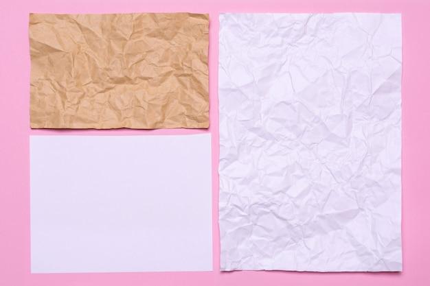 Vellen papier op een roze achtergrond. textuur van verfrommeld papier van verschillende grootte