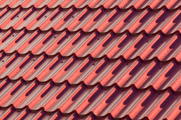 Vellen van oneffen rood metalen dak. close-up op een zonnige dag