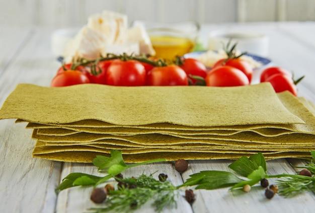 Vellen voor het koken van lasagne met spinazie, gestapeld in een stapel en ingrediënten: kerstomaatjes, kaas, boter, peper en kruiden. eten knollen.