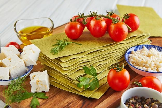 Vellen voor het maken van lasagne met spinazie en ingrediënten: kerstomaatjes, kaas, boter, paprika en kruiden.