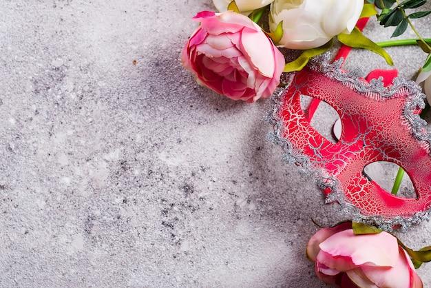 Venetiaans masker en bloemen op steenachtergrond. blind datumconcept, exemplaarruimte