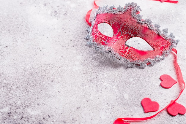 Venetiaans masker en valentijnskaartenharten op steenachtergrond.