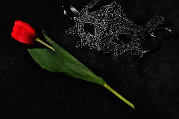 Venetiaans masker met een rode tulp in een donkere, suggestief verlichte omgeving. mysterieus liefdesconcept, san valentin-dag. Premium Foto