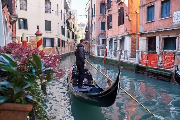 Venetië italië gondelier rijdt gondel door het smalle kanaal tussen kleurrijke huizen