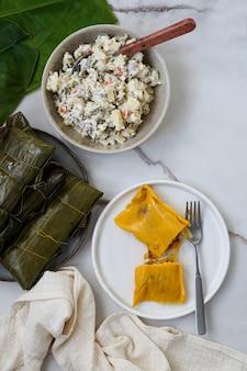Venezolaans kerstvoedsel - hallaca - maïsdeeg gevuld met een stoofpotje van varkensvlees en kip en kipsalade, ensalada de gallina