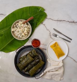 Venezolaans kerstvoedsel, hallacas, maïsdeeg gevuld met een stoofpotje van varkensvlees en kip en kipsalade
